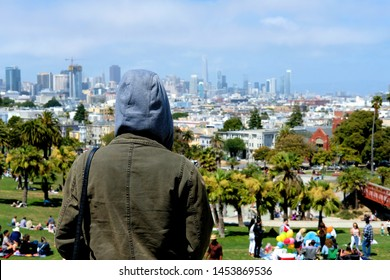 San Francisco, CA / US - July 7, 2019: Mission Dolores Park with a view of the San Francisco skyline in the distance; a hooded onlooker with his or her back to the camera looking to the distance.