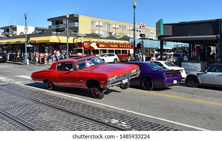 """SAN FRANCISCO, CA / USA - APRIL 30, 2017: Mexican Americans performing a """"three wheel motion"""" with a red blazing lowrider Chevrolet Impala in the streets of San Francisco."""