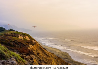 San Francisco, CA / USA - August 22, 2018: Silhouette of person hang-gliding over the ocean near Fort Funston at sunset in the fall