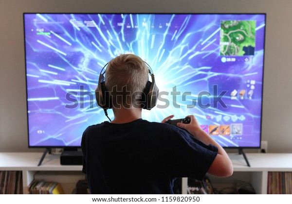 San Francisco, CA / USA - August 2018: A young man plays Epic Games' mega-hit Fortnite at home on his gaming system.