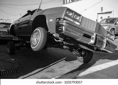 SAN FRANCISCO, CA, USA - FEBRUARY 25, 2018: A low rider classic car lifts its front wheel high off the ground.