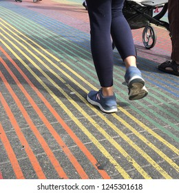 San Francisco, CA, USA March 7, 2018 A couple pushes a stroller through a rainbow colored crosswalk in the Castro District of San Francisco.  The crosswalk design was inspired by the gay Pride flag