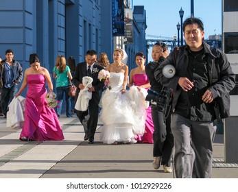 SAN FRANCISCO, CA, USA -  NOV 12, 2007: Happy Chinese wedding couple, Photographer and guests walk along The Embarcadero on Nov 12, 2007 in San Francisco.
