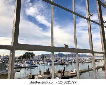 San Francisco, CA USA - November 26 2018: View out Fort Mason window looking at docked sailboats on bay