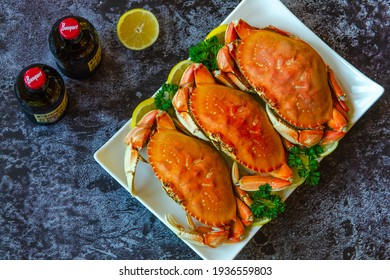San Francisco, CA, USA - October 17, 2020: Several bottles of Coors beer on the table. There are also three boiled crabs with lemon and parsley on a white plate.