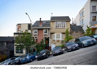 SAN FRANCISCO, CA, USA - OCTOBER 2017: A steep residential street with rows of houses stepping up the hill and cars parked on the street