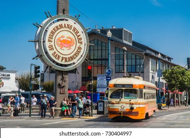 SAN FRANCISCO, CA, USA - SEP 11, 2017: Fisherman's Wharf Sign with an orange historic streetcar at Jefferson and Taylor. Fisherman's Wharf is a major tourist attraction in San Francisco.