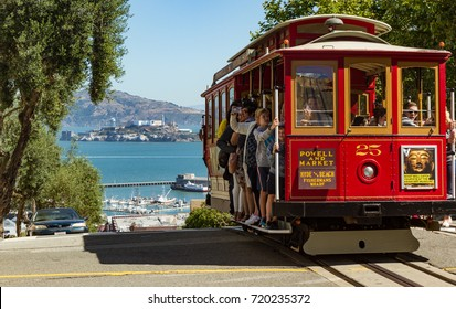 San Francisco cable car about to descend hill with Alcatraz in distance. Daytime photo, horizontal orientation. Photo taken in San Francisco, California, on July 7, 2017, at 9:17 AM.