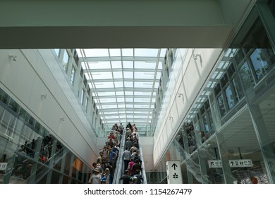 San Francisco, California - August 11, 2018: At the Salesforce Transit Center's grand opening, crowds ride the escalators from the bus level to the rooftop park.