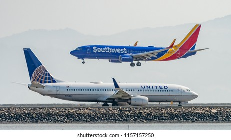 San Francisco, California - August 12th 2018: A Southwest Airlines plane comes into land as a United Airlines plane taxiis towards the end of the runway at San Francisco Airport.