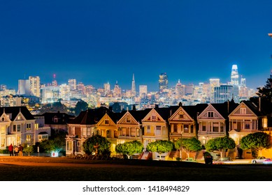 San Francisco, California - February 02 2019: Panted Ladies on the San Francisco hill with skyscrapers in the background at night