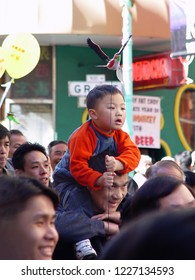 San Francisco, California - February 7, 2014: Little Asian boy sitting on his dad's shoulders watching the Chinese New Years Day festivities.