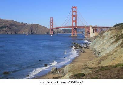 SAN FRANCISCO, CALIFORNIA: Golden Gate Bridge taken from overlook near Battery Crosby overlooking Marshall Beach as sailboat passes under bridge.