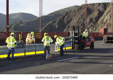 SAN FRANCISCO, CALIFORNIA  JANUARY  10, 2015: Unidentified workers install movable median barrier sections on the Golden Gate Bridge.