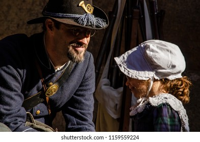 San Francisco, California - January 27, 2018: Union soldier dressed in blue uniform talking to little girl wearing a bonnet participating in Civil War re-enactment event at Fort Point in San Francisco