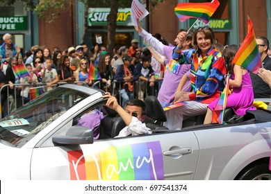 San Francisco, California - June 26, 2016: Nancy Pelosi and her husband Paul ride in a vehicle in the annual San Francisco Pride Parade on Market Street.
