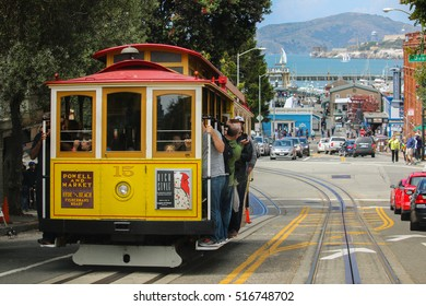 San Francisco, California - Mai 23, 2015: Tourists riding on the iconic cable car, blue sky day at top of Hyde Street view overlooking the bay water and Alcatraz prison
