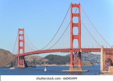 SAN FRANCISCO, CALIFORNIA - NOVEMBER 1, 2010: Golden Gate Bridge taken from Baker Beach on November 1, 2010, as a sailboat passes under bridge. Location is well known location near Golden Gate Park.