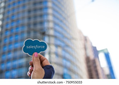 San Francisco, California - November 6th, 2017; A woman is holding up a Salesforce sticker in front of the Saleforce Tower on the corners of 1st, Mission and Fremont Streets.