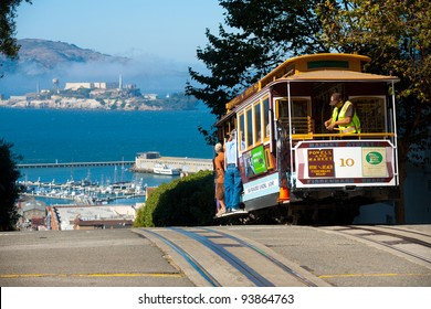 San Francisco, California - September 21, 2011: Street cable car, an iconic mode of transportation, going downhill to meeting Alcatraz Prison at the top of Hyde Street