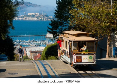 San Francisco, California - September 21, 2011: Tourists riding on the iconic cable car on clear sunny, blue sky day at top of Hyde Street view overlooking the bay water and Alcatraz prison