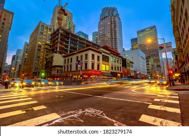 San Francisco, California, United States - August 15, 2019: Crossroad of San Francisco downtown by night. Light trails of cars in city traffic and Californian nightlife.