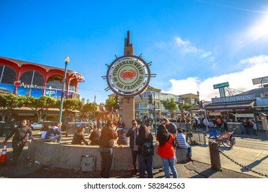 San Francisco, California, United States - August 14, 2016: people at Fisherman's Wharf square under the famous signboard of San Francisco. Fisherman's Wharf is a neighborhood and famous waterfront.