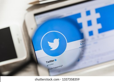 San Francisco, California, USA - 14 March 2019: Twitter, social network official website homepage under magnifying glass. Concept Twitter, social network logo visible on smartphone, tablet screen