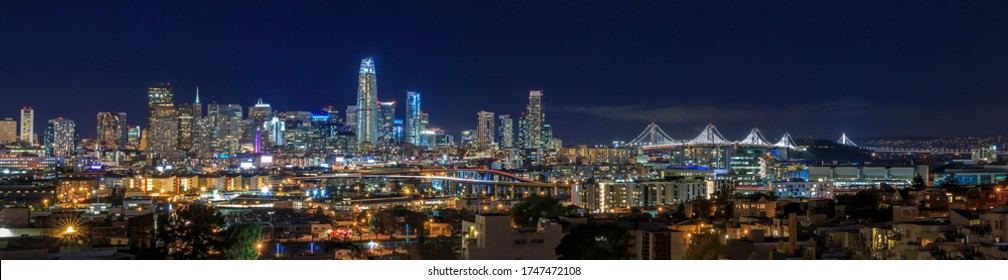 San Francisco, California, USA - April 8, 2017: San Francisco city skyline panorama after sunset with city lights, the Bay Bridge and highway light trails leading into the city