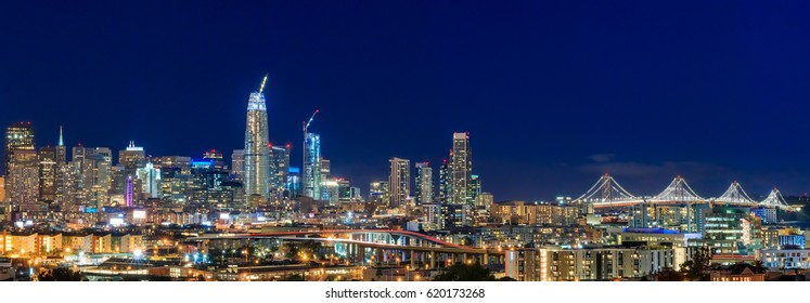 San Francisco, California, USA - April 8,2017: San Francisco city skyline panorama after sunset with city lights, the Bay Bridge and highway trail lights leading into the city