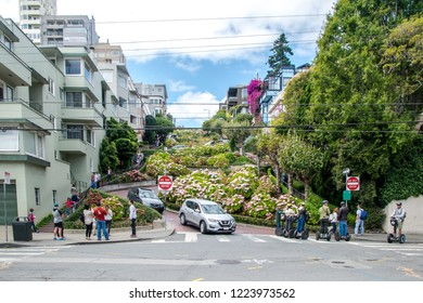 San Francisco, California, USA - August 29th 2018 - Tourists doing a motor scooter tour on lombard street