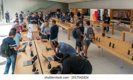San Francisco, California, USA - August 2019: People examining Apple products laptops phones and tablets at Apple Store in Union Square