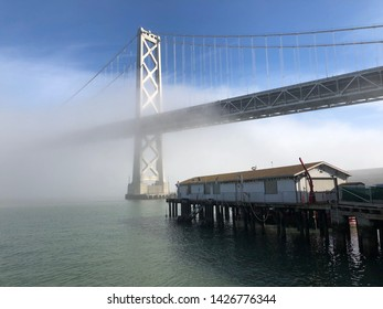 San Francisco, California / Usa - Jannuary 20 2019: Bay bridge on foggy day with pier below in the foreground