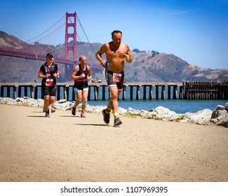 San Francisco, California, USA - June 3, 2018: Triathletes run to the finish with the Golden Gate Bridge in the background during the 2018 Escape From Alcatraz Triathlon.