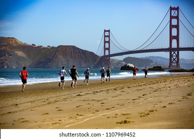 San Francisco, California, USA - June 3, 2018: Racers run along Baker Beach with the Golden Gate Bridge in the background at the 2018 Escape From Alcatraz Triathlon.