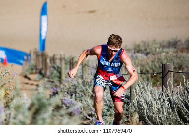 San Francisco, California, USA - June 3, 2018: Jarrod Shoemaker searches for footing on the sand ladder as he races to fifth place at the 2018 Escape From Alcatraz Triathlon.