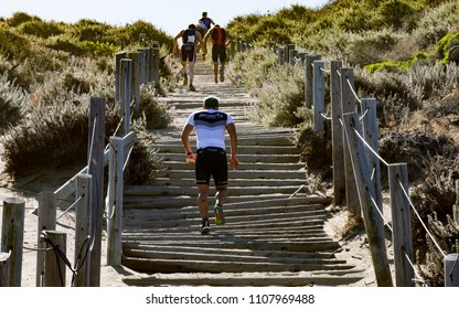 San Francisco, California, USA - June 3, 2018: Triathletes climb the sand stairs at Baker Beach during the 2018 Escape From Alcatraz Triathlon.