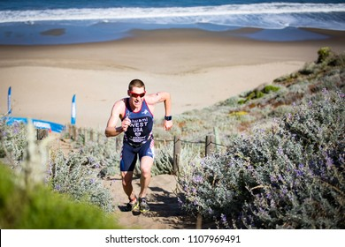 San Francisco, California, USA - June 3, 2018: Jason West makes running up a cliff made of sand look easy en route to his third place finish at the 2018 Escape From Alcatraz Triathlon.