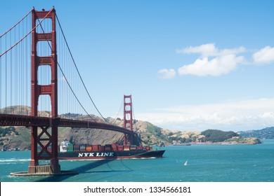 SAN FRANCISCO, CALIFORNIA, USA – JUNE 11,2017: Container cargo ship under Golden Gate Bridge in San Francisco Bay, California, USA.