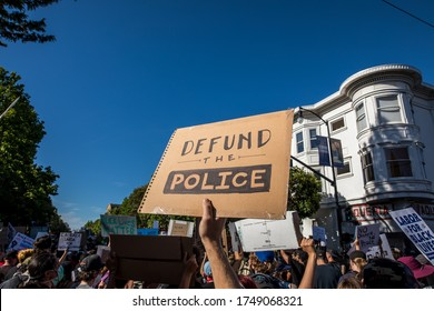 """San Francisco, California, USA, June 03, 2020, Protest after George Floyd death, Black Lives Matter group standing against police and carrying a banner sign """"Defund the police"""""""