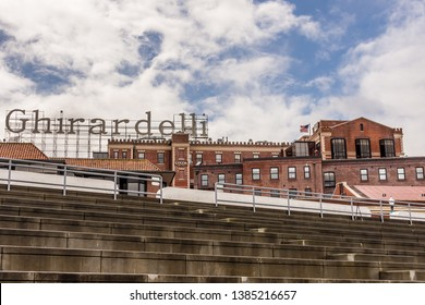 San Francisco, California / USA - March 15, 2018: View of Ghirardelli Chocolate Company from the Aquatic Park bleachers under a cloudy sky