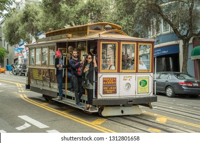 San Francisco, California, USA - May 2016: Famous Cable Car Trolley Car on the streets of the city, people standing on the side