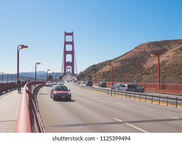 San Francisco, California, USA, October 2017. Vehicle traffic on the San Francisco bridge road. People carry out sports by bicycle along the walkway on the aforementioned bridge
