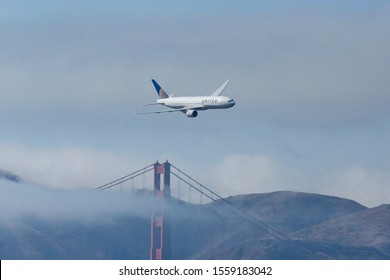 SAN FRANCISCO, CALIFORNIA, USA - October 25, 2019: A United Airlines 777 enters the San Francisco bay area with the Golden Gate Bridge in the background during Fleet Week in San Francisco.