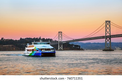 SAN FRANCISCO, CALIFORNIA, USA - OCTOBER 26, 2017: San Francisco ferry and Oakland Bay Bridge in the evening