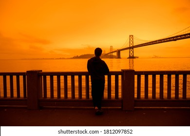 San Francisco, California, USA, September 09, 2020, San Francisco Downtown people with bay bridge yellow orange sky glowing due to air pollution pacific ocean scaffolding