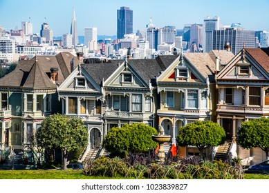 San Francisco, California-circa 2014-Dancing Ladies row of cute gingerbread victorian architectural style homes on hill in San Francisco with modern buildings and city in background