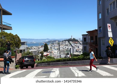 San Francisco, California/USA- 04.22.2019- Tourists at the top of Lombard street, the famously crooked street with views all the way to Telegraph hill.