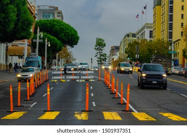 San Francisco, California/USA-11/15/17: Van Ness Improvement Project showing orange barriers on Van Ness and Jackson streets as on coming cars have lights on adriving on a wet road