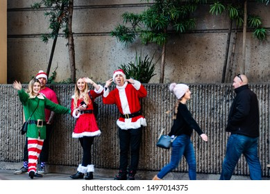 San Francisco, California/USA-12/8/2019: SantaCon 2018 or Santarchy people parcipating on a pub crawl, parading in santa costumes on Stockton Street while casual dressed couple walks by the party
